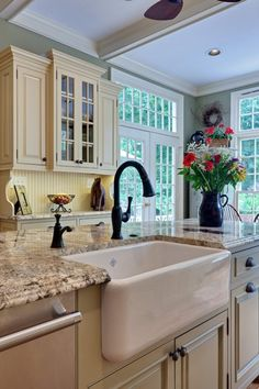 cream cabinets/green-grey walls/white woodwork/transom windows