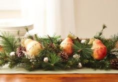 For a fruitful centerpiece, cut and weave together a few strands of artificial evergreens. More Christmas centerpieces: http://www.midwestliving.com/homes/seasonal-decorating/easy-christmas-centerpiece-ideas/?page=10