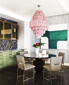 Gorgeous pink chandelier and green accents in dining room