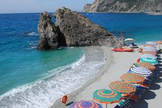 Monterosso Beach: The sole sandy spot in picturesque Cinque Terre, nestled amongst rocky outcroppings and populated by festive striped umbrellas.