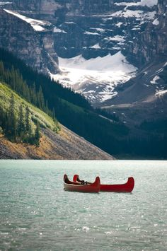 Green trees and red canoes with a frosting of sunshine sparkle on the water - Lake Louise - Banff - #GILoveAlberta