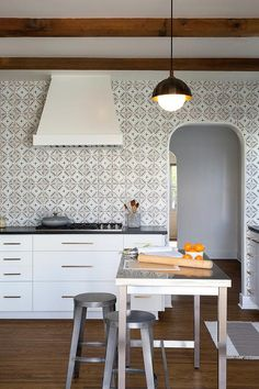 Rustic inspired kitchen with exposed wooden beams, a retro pendant light, and a wall of patterned tile