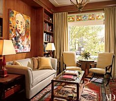 In the library, the team preserved an original stained-glass window. Its hues complement those of the carpet and stand out against the room's new chestnut paneling. The painting is by Hung Liu. Wool drapery sheer, Rogers Goffigon. Lamps from Yale R. Burge | archdigest.com