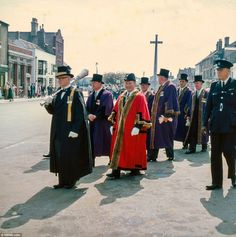 Procession:  A group of officials carry a torch through the street in front of onlookers on Market Hill, St. Ives, in 1960