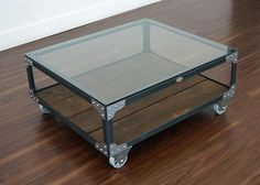 """Industrial Coffee Table - Aircraft Factory Cart Coffee Table - Featuring a gloss clear coat steel finish, a walnut color wood shelf stain and a 3/8 inch clear glass table top. Made from steel angle iron, rough sawn white pine with a tempered glass table top.  Fastened with rivets and accent corner brackets, mounted on 5 inch casters with a decorative vintage style brass boilerplate on front. 40"""" L x 34"""" W x 17"""" H, 135 lbs. Duty Free."""