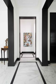 Thin black tiles are inset in the gray marble floor to define the hallway in this chic black-and-white home. Abstract art makes a bold statement at the end of the hall.