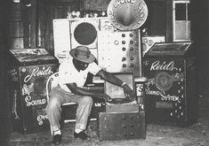 """Duke Reid, acompañado del equipo de sonido de su Trojan. Esos gigantes altavoces que le rodean eran conocidos como """"houses of joy"""". Construidos por el célebre ingeniero de sonido jamaiquino Hedley Jones, estas máquinas eran las responsables de los poderosos graves que se podían escuchar -y sentir- en esas fiestas"""
