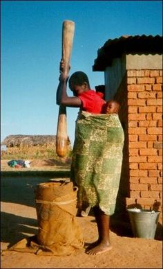 Malawi - Babywearing mother prepares msima, the staple food of Malawi