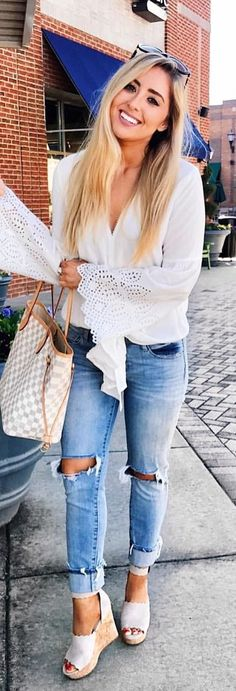 #spring #outfits  smiling woman in white long-sleeved shirt standing on concrete floor during daytime. Pic by @alexaelizabeth_