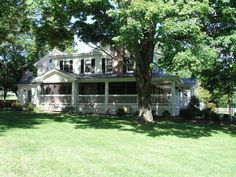 Farmhouse with pretty wrap around porch - looks like part of it is screened in
