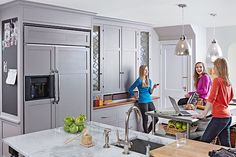 Custom gray cabinets cover the fridge in this spacious kitchen, and incorporate leaded-glass sidelights that the owner bought years ago at an antiques fair, plus a magnetic chalkboard for notes.