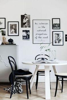 decoração de sala de jantar com posters em preto e branco, mesa redonda branca com cadeiras pretas