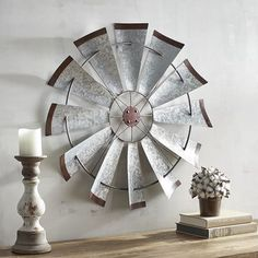 """Frequently seen on farms of yesteryear, the windmill stood tall above the fields of corn and beans. We've used this iconic symbol and developed a vintage-style piece of wall art for your family or living room. Crafted of iron, it's near life-size at 30"""" diameter. A Pier 1 exclusive."""