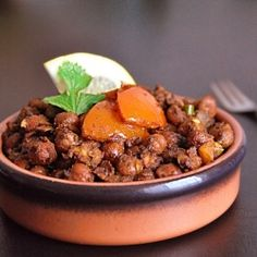 Rawalpindi style curried chickpeas with mild spices and a tangy kick, garnished with tomatoes.