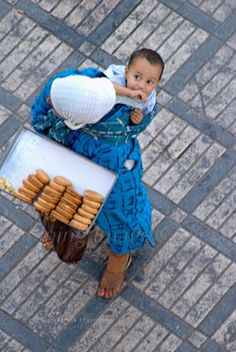 Baby on mother's back while she's selling cakes at Djemma el Fna seen from above just as the boy looks up
