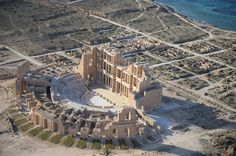 Aerial view of the almost intact ancient Sabratha Theatre located in Sabratha, Libya, on the Mediterranean coast. The site was originally a Phoenician trading-post, but became part of the Roman Empire, and its monuments were built in the 2nd and 3rd centuries AD. View on Google Maps. (© Jason Hawkes)