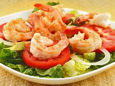 Shrimp Cocktail Salad: A main-course salad of sauteed shrimp, romaine lettuce, sliced tomatoes, sweet onion and avocado topped with a light, creamy version of a classic cocktail sauce for dressing.