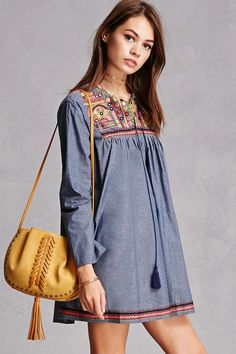 A chambray woven tunic by Velzera™ featuring an ornate embroidered yoke with high-polish accents, a split tassel drawstring neckline, long sleeves, and an embroidered hem.