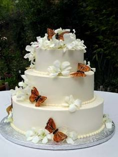 Round three tier white buttercream wedding cake decorated with orange butterflies - https://www.facebook.com/different.solutions.page
