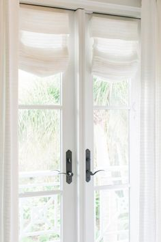 Simple, wispy, white window treatments hang on the French doors leading out to the small balcony off the master suite bathroom.