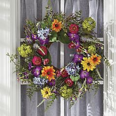 Classic Summer Wreath | A profusion of colorful summer flowers, crafted of fabric and plastic, are intertwined on a natural vine wreath.