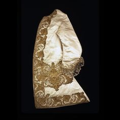 Long-sleeved waistcoat, England, c. 1740. Cream silk satin, heavily embellished with bold scrolling designs in silver-gilt needlework down fronts, around pocket flaps, at front hem and around edge of sleeves.