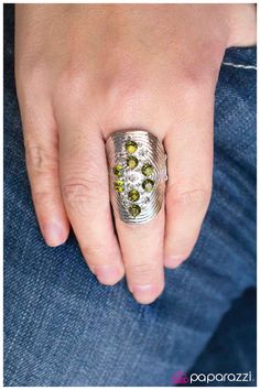 An elongated silver plate is etched with symmetrical lines of texture and topped with a cluster of glistening faceted beads and raised spikes in a green finish.  Sold as one individual ring.