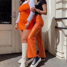 Pair of trendsetters highlighting orange statement pieces. Orange mini dress, white long sleeve, tall white boots, orange shiny pants, black sneakers, black short sleeve. Visit Daily Dress Me at dailydressme.com for more inspiration women's fashion and trends. Street style, New York fashion, summer trends, summer outfits, trendsetters, mini dress, pants, sneakers, tall boots, orange, bright, statement pieces. White Boots, Tall Boots, Daily Dress Me, New York Street Style, Black Sneakers, Summer Trends, White Long Sleeve, New York Fashion, Casual Chic