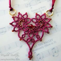 A red 6 mm round glass bead is nestled in the center of this deep rose color tatted lace heart, with iridescent glass seed beads worked in for extra