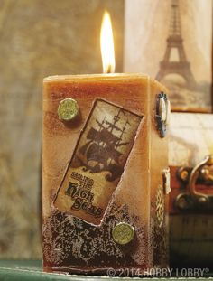 """This shipshape pillar candle features a bounty of pirate paraphernalia, including paper images (same technique as used on """"what an eye-full"""" above) and coin bullion brads. The golden sunset glow comes from easy-to-use candle dye."""