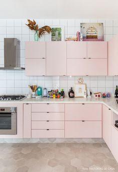 Cozinha com piso de ladrilhos hexangulares tem armários rosas e azulejos brancos.