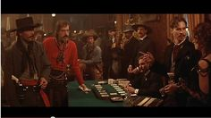 Tombstone (1993) The Drinking Scene: A sweaty, sick-looking Doc Holliday (Val Kilmer) meets Johnny Ringo (Michael Biehn) in a bar and wastes no time verbally abusing him. While sipping a brew. Then Ringo takes out his gun and flips it around a bit - prompting Doc to show off some considerable skill with his tin cup.