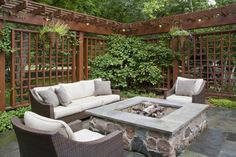 This wonderful outdoor seating area featuring a custom built in gas fire pit with elegant wooden outdoor privacy screen was designed by Rolling Landscapes Inc