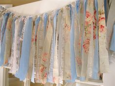 This piece is made from strips of hand cut beautiful vintage floral fabric, white lace, and pale blue cotton fabric. The edges were left raw, unfinished, and slightly frayed to add to the shabby chic feel of this garland. The fabric is secured to a sturdy natural jute cord with an