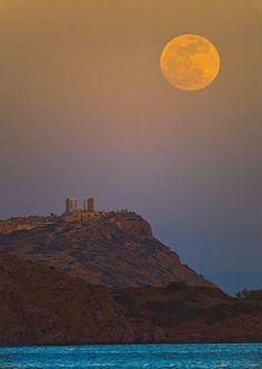 スーパームーン2012(アテネの満月):  - Photograph by Anthony Ayiomamitis     ギリシャ、アテネ南部のスニオン岬に建つポセイドン神殿。  夕暮れの空にスーパームーンが現れた(5月5日撮影)    地球を楕円軌道で周回する月は、ほぼ30日毎に最も接近する  「近地点」に至る。    「スーパームーン」という言葉は1979年、近地点の満月を表すために考案された。  遠地点も同様のペースで通過する。     5日、月は地球から35万6955キロまで接近した。    米東部標準時の午後11時34分(日本時間6日午後0時34分)に満月を迎え、そのわずか1分後に近地点に到達している。     アメリカ、イリノイ州シカゴにあるアドラープラネタリウムの天文学者ゲザ・ギュク氏は、    「年内の通常の満月と比べ、16%大きく、30%明るく見える。大したことはないと思うかもしれないが、明らかにいつもより大きく感じるはずだ!」    と予想していた