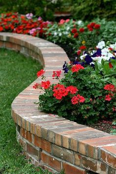 Brick flower bed border doubling as a casual bench. Convenient when planting. Small retaining wall with brick on edge capping. Nice brick colors. Better straight, not curved, for our space. Front yard by the porch and sidewalk.