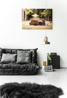 white floor | white walls | black rug | black sofa | industrial pendant light | wall art | gray pillows