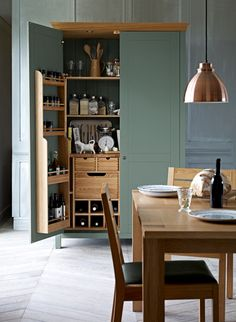 The Padstow larder in a green painted finish is made from solid oak and features drawers, shelves and a wine rack