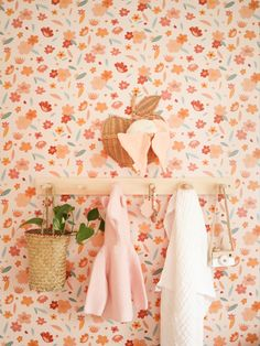 Easiest DIY nursery peg rail with pale wood. Cutest decor with a hanging plant, cozy knit sweater, baby blanket and toy camera.