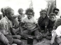 Members of the group listen to a radio. Picture: Peter Ward