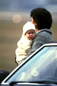 March 25, 1985: Prince Harry carried by his nanny Barbara Barnes at Aberdeen airport in Scotland.