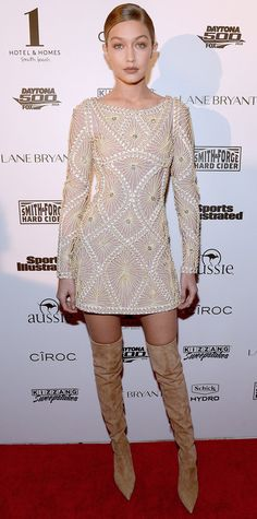 Gigi Hadid stopped by the Sports Illustrated Swimsuit 2016 BBQ Party in a nude mosaic lace Herve Leger by Max Azria dress complete with tan suede thigh-high boots.