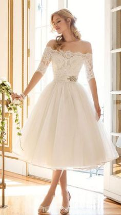 Classy off-the-shoulder tea-length white wedding dress with lace quarter length sleeves; Featured Dress: Justin Alexander