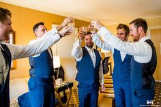 San Diego wedding at lomas santa fe country club groom and groomsmen navy blue suits with matching vests and white dress shirt with white bow tie and white floral boutonnieres toasting their drinks before ceremony