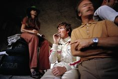 Jochen Rindt smokes a cigarette in the pits alongside his wife Nina and Lotus team boss Colin Chapman. Austrian GP '70
