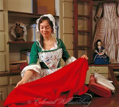 Woman displays a bolt of red cloth in the Margaret Hunter Millinery shop.