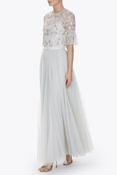 This signature cropped top is designed to style perfectly with our high waisted tulle skirts. The top is created in semi sheer tulle with subtly fluted sleeves. A separate camisole slip is included. The pretty, subtly shimmering artwork creates an all-over covering effect, using clusters and a trailing of silver cut flowers and naive shapes, creating a constellation style effect.
