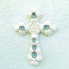 White Cross Seashells with Turquoise Aqua blue Accents Wall Crucifix Religious Christian Gift. Pure and simple white seashell cross with pure white cardium shells and aqua limpet accents hangs from gator hanger and measures about 11 inches high and 8 inches wide. Accented with a white mini sand dollar center and edged in tiny white cardium shells this is a great gift for any religious occasion as well as for a cross collector. Hangs from a gator hanger on the back. Will come to you very…