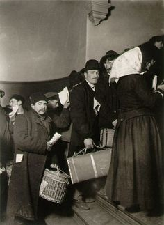 Ellis Island - They look tired & very suspicious of the camera.  Notice the shoes on the man with the rectangular suitcase.