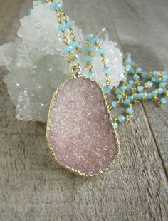Sparkling jasper quartz druzy pendant is accentuated by serene blue green chalcedony roundels to create to create this beautiful statement necklace. This color combination is so pretty! Natural druzy pendant is a beautiful pink sand color and sparkles brilliantly. It is wrapped in gold leaf for a polished finish .